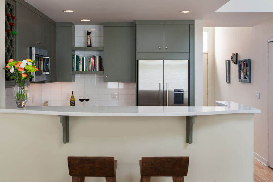 Kitchen with grey shelves to the ceiling and a curved white countertop with bar height stools - designing a custom kitchen - Teknika Kitchens and Baths